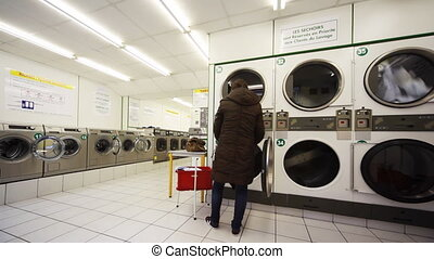 Large washing machines, woman puts in drum clothes - public...