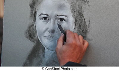 Street painter draws charcoal on canvas portrait of girl