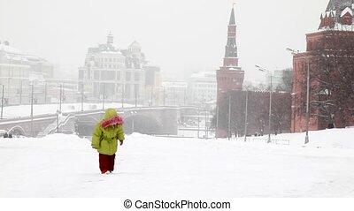 Girl plays with snow near Moscow Kremlin under snowfall