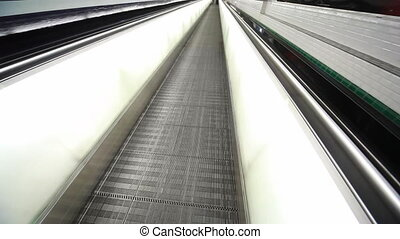 Escalator and feet of people walking on it in Paris airport