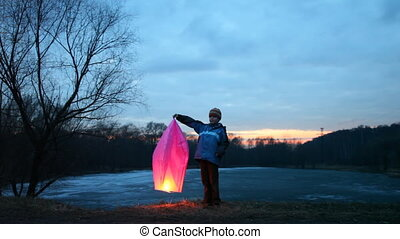 boy holds chinese lantern, comes father, takes it from him,...