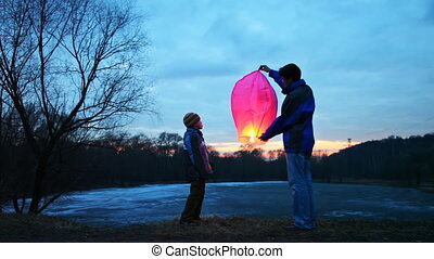 man holds chinese lantern of winter forest, its son looks and touches it, part2