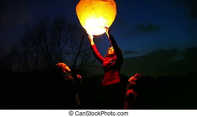 woman holds glowing chinese lantern, son and daughter look