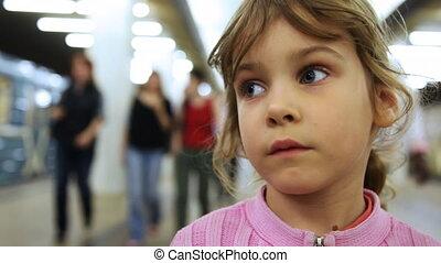 Cute little girl stands inside subway - cute little girl...