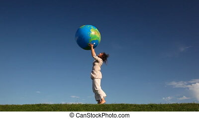 Woman tosses inflatable earth standing at grass - pretty...