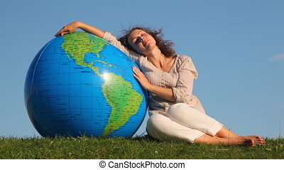 cute girl with closed eyes sits relaxing in grass and rests on large inflatable ball at form of Earth against sky summer