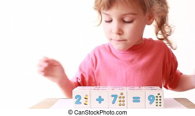 Girl play wooden blocks with numbers, builds wall of cubes