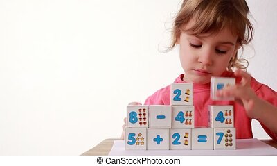 Girl puts wooden bloks with numbers, adds cubes