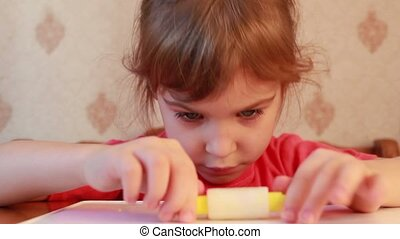 Girl rolls cylinder of plasticine on table - beautiful girl...