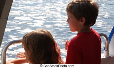 Boy and his sister float fast moving boat hydrofoil on sea -...