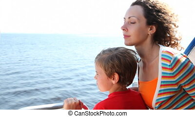 Mother and son float fast moving boat hydrofoil on sea -...