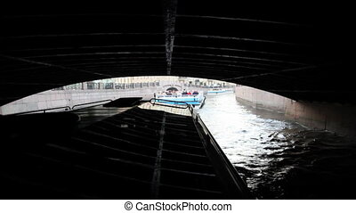Boat floats of darkness by channel from wide bridge to St. Petersburg