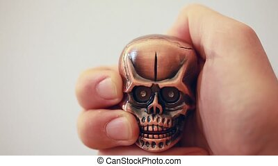 Revolving lighter in shape of tiny cranium with glow eyes in hand