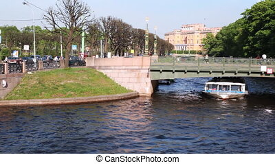Boat floats under 2-nd Garden Bridge over channel in center of St. Petersburg