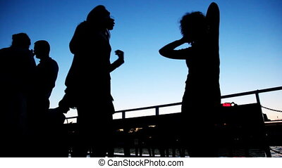 Silhouettes of two girls dancing on board ship sailing at...