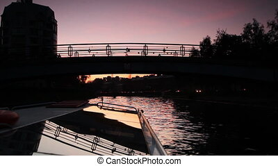Boat floats under small bridge in St. Petersburg at night -...