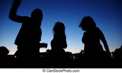 Silhouettes of young girls dancing on board ship sailing -...