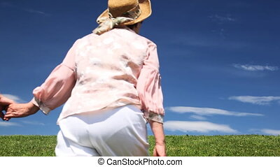 Mature couple holding hands leaves over grass - mature...