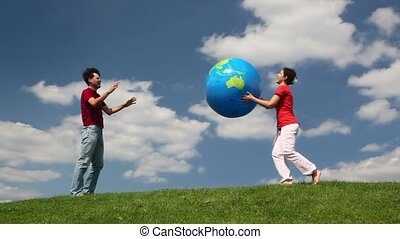Man and woman playing big inflatable ball on a meadow