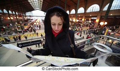 Woman looks at map in Paris North Station - young woman...