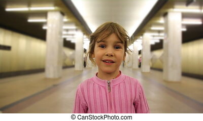 Little girl stands in subway passage, closeup