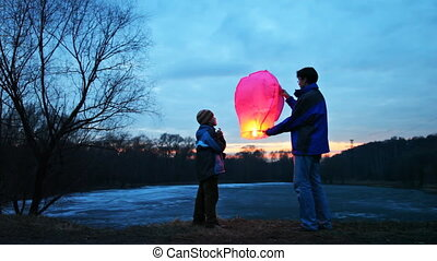 man holds chinese lantern, son looks at it, then daughter...