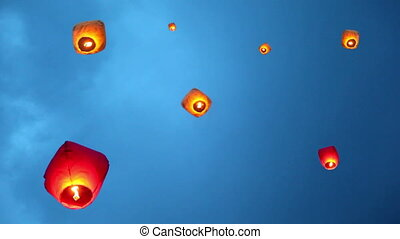 glowing chinese lanternes with burning flame inside flies...