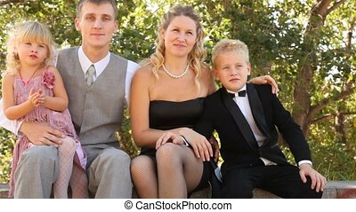 Family in celebratory clothes sits on a bench. - Family with...