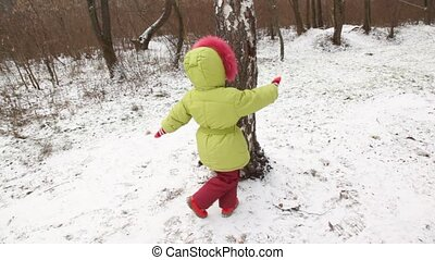 Cute little girl dances round tree.
