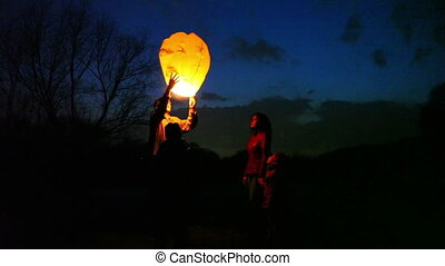 man does attempt to start glowing chinese lantern, then gives its wife, son and daughter look, part3