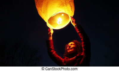 woman holds above head glowing chinese lantern - young woman...