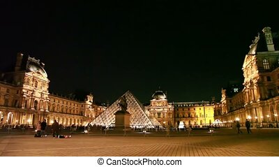 Tourists walk on square in front of Louvre, night