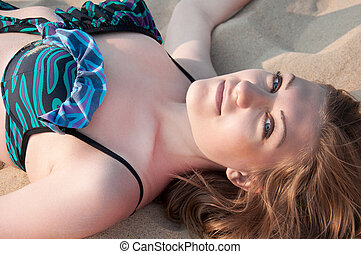 beautiful Woman in a bathing suit lying on the sand