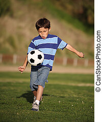 Latino boy playing with soccer ball - Authentic happy Latino...