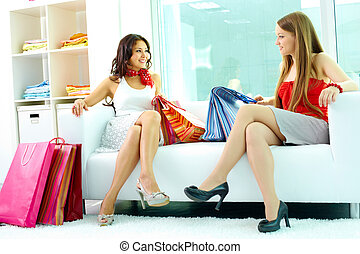 After shopping - Portrait of happy girlfriends looking at...