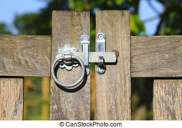 Close up closed latched wooden gate on a sunny day