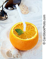 orange with a straw in the beach