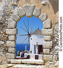 Windmill through an old Venetian window, Greece