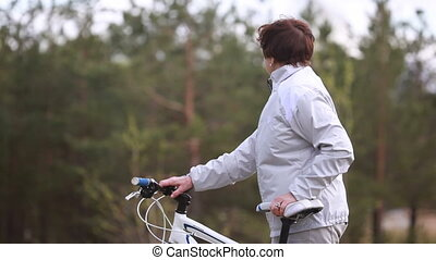 Active husband - Senior woman looking at her husband riding...