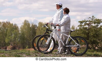 Seniors with bicycles - Senior couple standing with their...