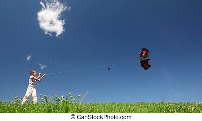 Boy plays kite in meadow against blue sky