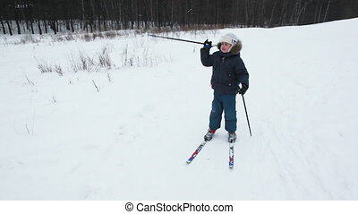 boy stands on skis at winter wood and shows somewhere ski...