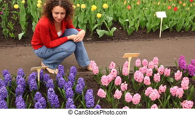 Woman sits looking at beautiful hyacinths