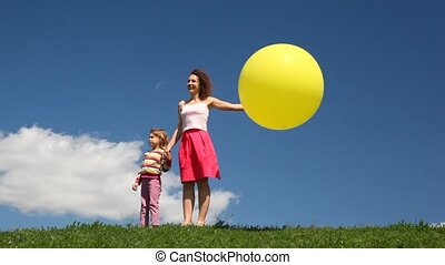 Woman with daughter and bubble stand on meadow