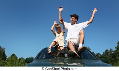 father and son sitting on roof of car, then they waved with...