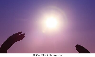 hands of man and woman touching against sky with sun