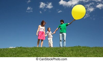 Family holding yellow bubble hands down hill