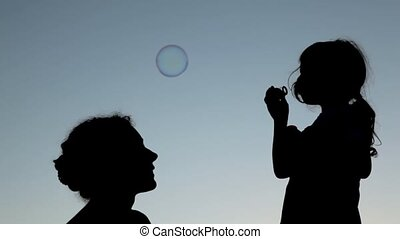 mother sitting near little girl blowing up soap bubbles