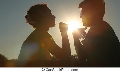 silhouettes of couple sits on bench and talks
