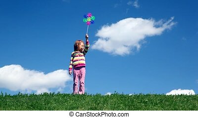 Girl stands with wind propeller on grass meadow